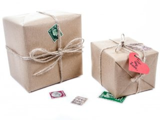 two packages wrapped in brown paper with twine ribbons