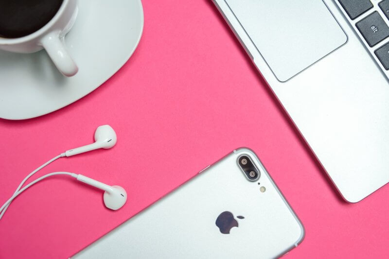 iPhone, earphones, coffee, and laptop on pink background